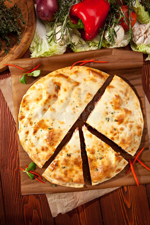 Calzone. Pizza Calzone with Chicken and Vegetables on Parchment stock photos