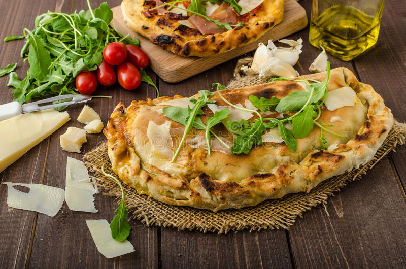 Calzone pizza. Filled herbs, cheese and tomatoes royalty free stock photo