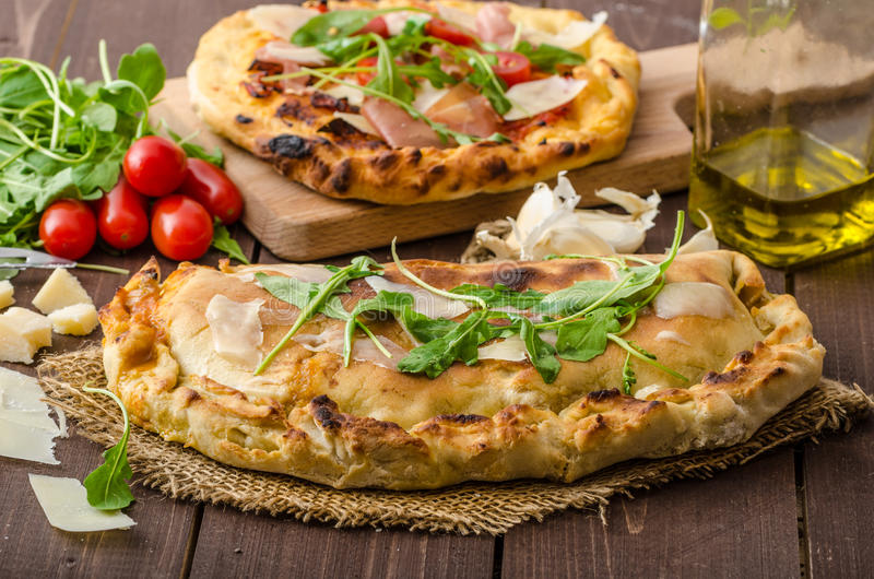 Calzone pizza. Filled herbs, cheese and tomatoes royalty free stock image