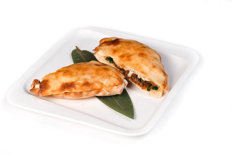 Calzone pizza halves on bamboo sheet in plate on isolated white background. Calzone pizza halves on bamboo sheet in square plate on isolated white background royalty free stock image