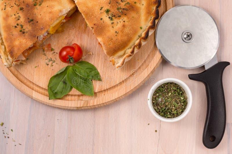 Calzone pizza i rolownika nóż na lekkim drewnianym tle obraz royalty free