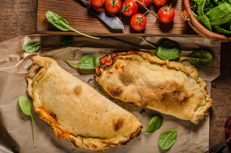 Calzone pizza rustic. Calzone pizza, stuffed with tomato and herbs sauce, baked to crispy royalty free stock photography