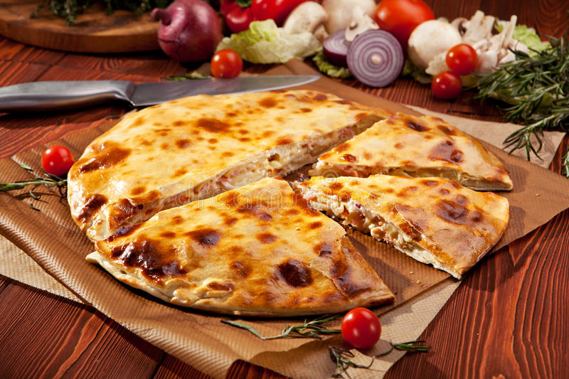 Calzone. Pizza Calzone with Salmon on Parchment stock image