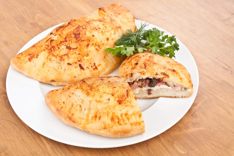 Calzone Pizza. Twp Calzone Pizzas on White Plate on Wooden Table stock photography