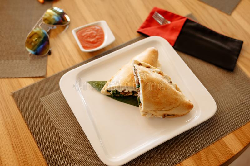 Calzone pizzy po??wki na bambusa prze?cieradle w kwadrata talerzu na drewnianym stole obrazy stock