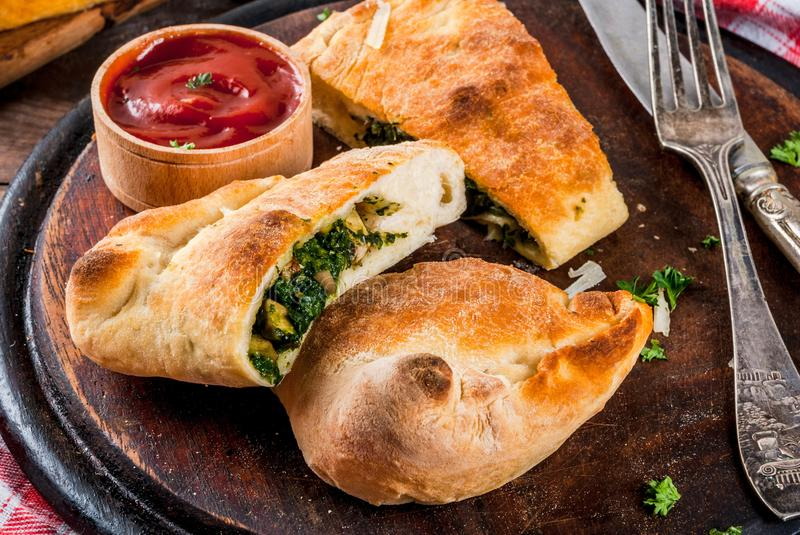 Calzone with Spinach and Cheese. Italian food, closed pizza calzone with Spinach and Cheese, wooden background, copy space stock photo