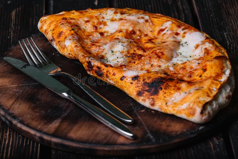Calzone - Stuffed Pizza. Fork and knife on the cutting board stock images