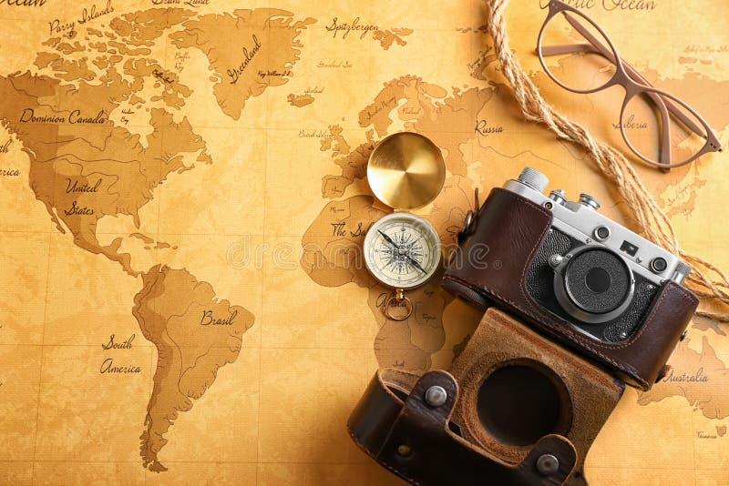 Caméra, boussole et verres de photo sur la carte du monde de cru Concept de planification de voyage images libres de droits