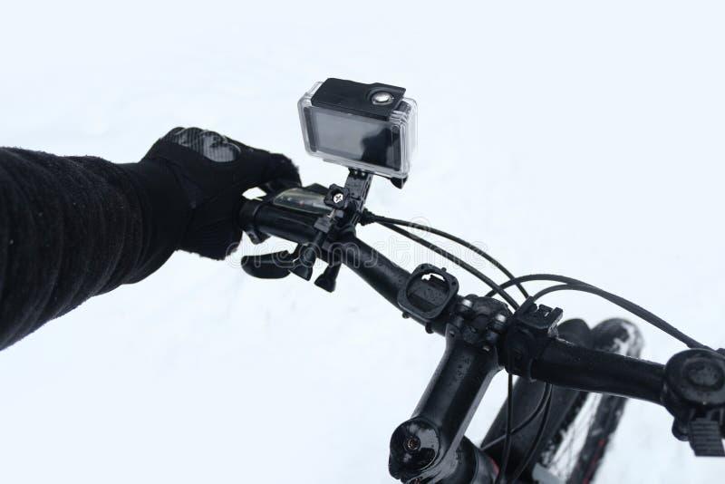 Caméra d'action sur une bicyclette dans un cas protecteur Le type dans les gants monte une bicyclette pendant l'hiver sur une nei photo stock