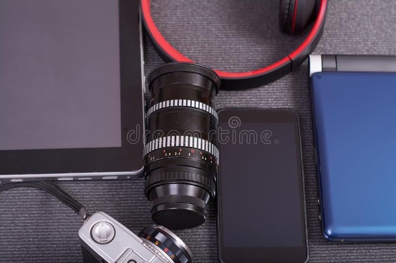 Caméra de photo de cru à côté d'un ordinateur portable un comprimé et un smartphone photos stock