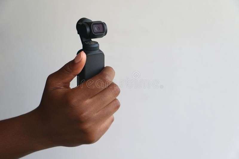 Caméra de poche tenue dans la main de dji d'osmo photographie stock libre de droits