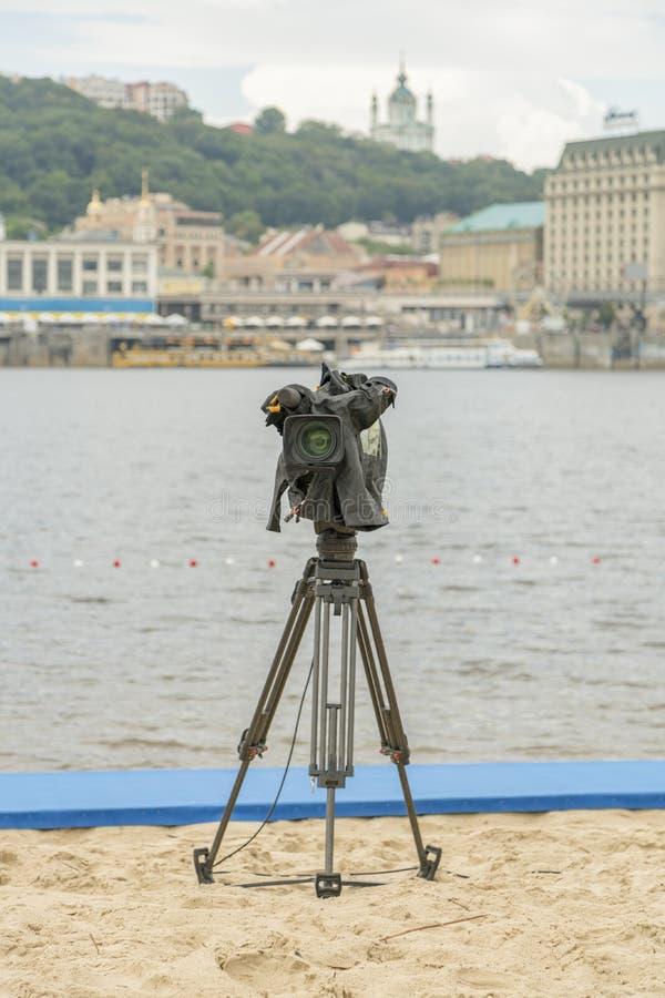 Caméra de télévision sur la plage de rivière Caméscope isolé sur un trépied Photo verticale photos stock