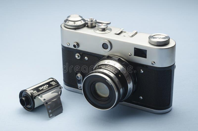 Cam?ra de vieux film de cru et film analogues de 35mm sur le fond bleu image stock
