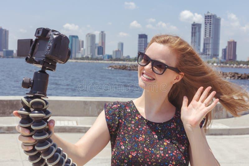 Caméra enregistrant un jeune blogger féminin caucasien faisant des gestes tout en faisant une vidéo photos libres de droits