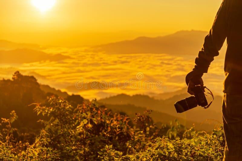 Caméra professionnelle de participation de photographe d'homme de silhouette pour la prise une photo la montagne image stock