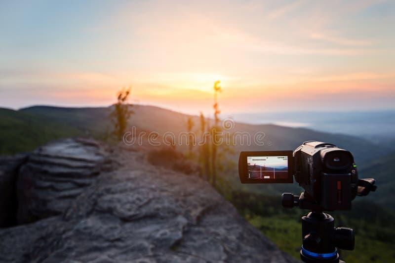 Caméra vidéo de Digital sur le lever de soleil de pelliculage de trépied aux montagnes photographie stock