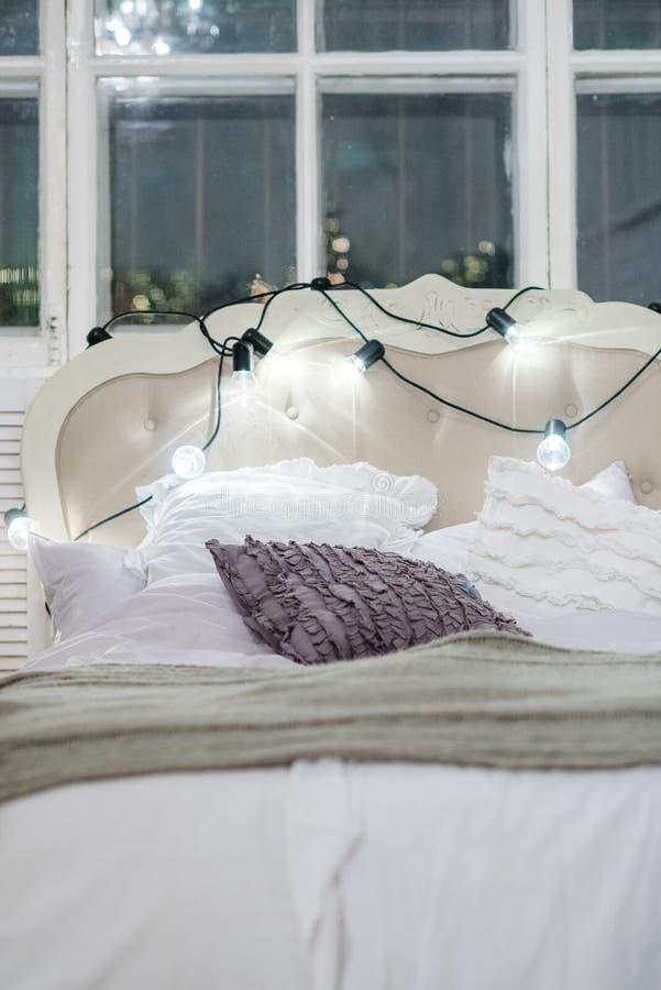 Cama acolhedor branca com descanso do vintage e luzes de Natal, defocus imagens de stock royalty free