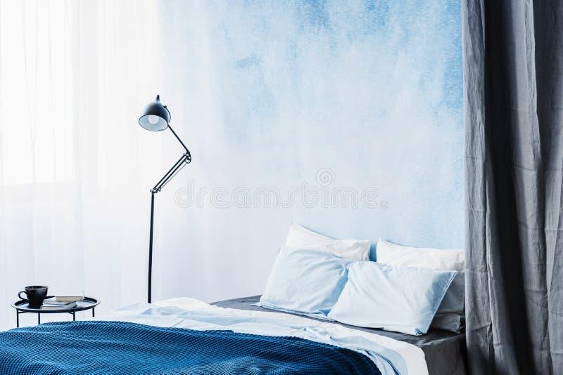 Cama azul entre a lâmpada e a cortina cinzenta no interio simples do quarto imagens de stock