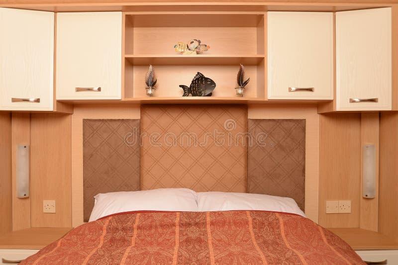 Cama com prateleiras e gabinetes fotografia de stock royalty free