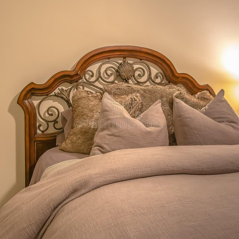Cama con el cabecero de madera y del hierro labrado dentro del dormitorio de un hogar foto de archivo