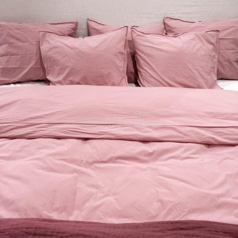Cama con las ropas de cama rosadas fotos de archivo