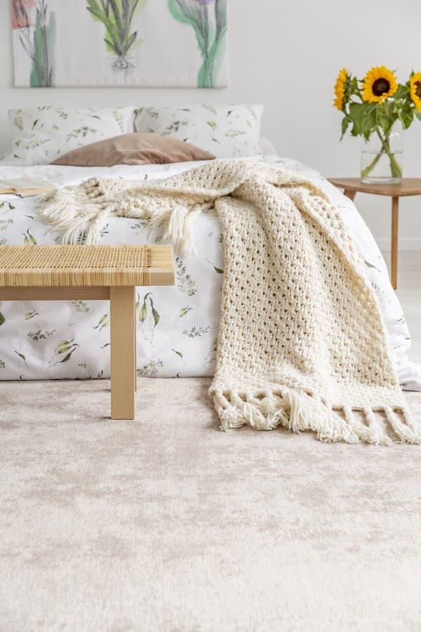 Cama confortável com as folhas orgânicas e a cobertura do algodão que estão em um tapete macio em um interior pastel do quarto foto de stock