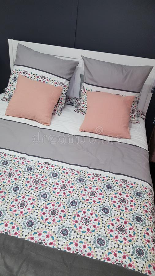 Cama confortável com coberta do projeto e os descansos cor-de-rosa no interior cinzento do quarto fotografia de stock royalty free