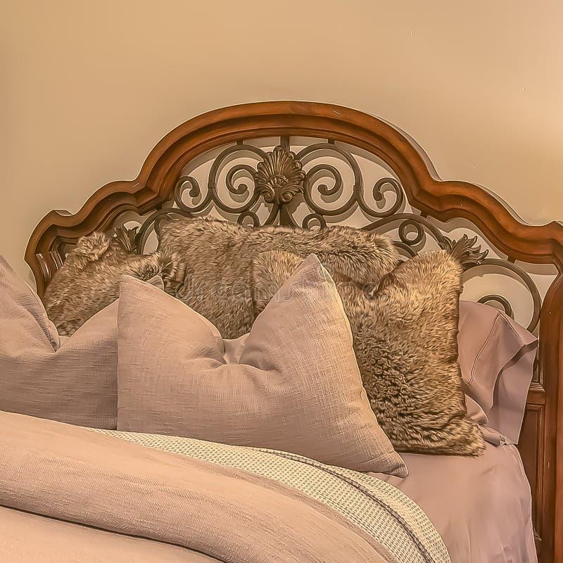 Cama cuadrada con las almohadas mullidas contra el cabecero de madera y del hierro del worught fotografía de archivo libre de regalías