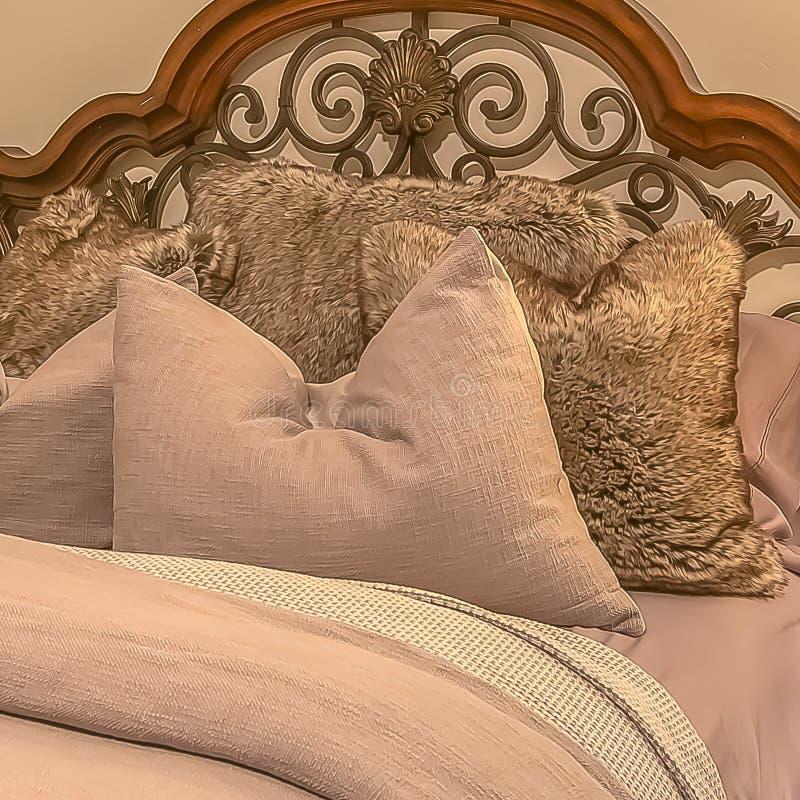 Cama cuadrada del marco con las almohadas mullidas contra el cabecero de madera y del hierro del worught fotos de archivo libres de regalías