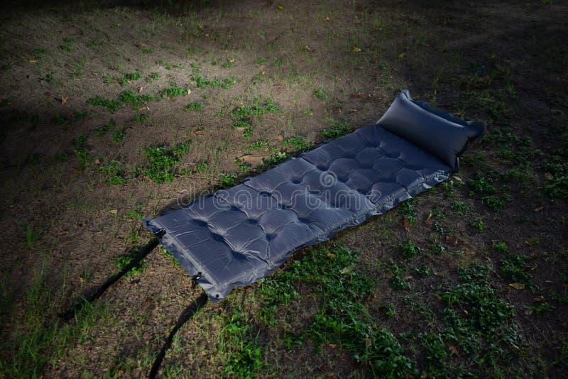 Cama de acampamento inflável cinzenta na terra na noite acampamento na obscuridade fotografia de stock