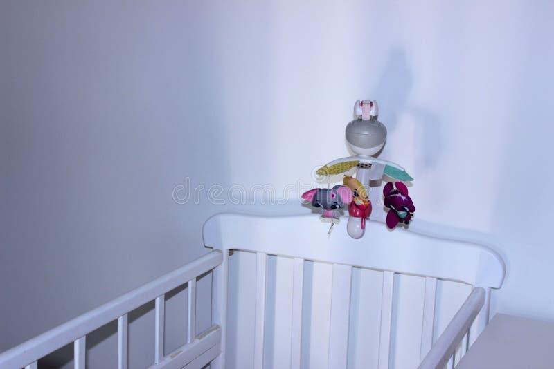 Cama de bebé blanca para recién nacido sobre el fondo blanco de la pared Interior blanco para el baby boom fotos de archivo