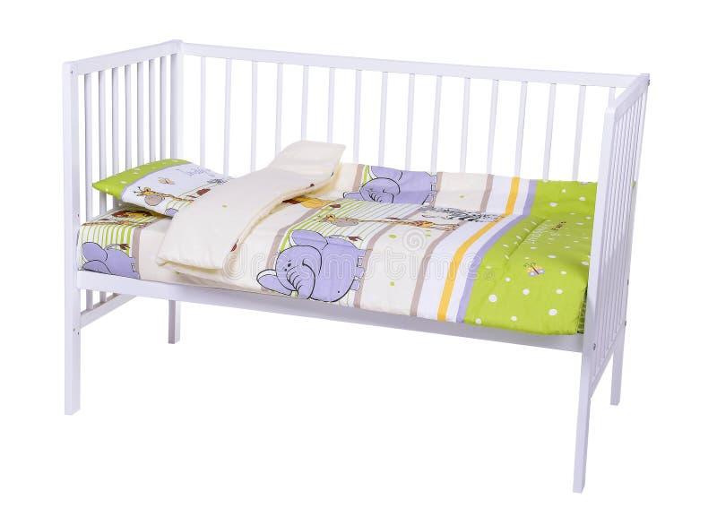 Cama de bebé en blanco imagen de archivo