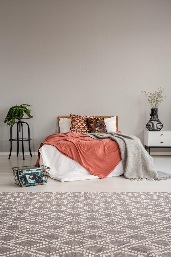 Cama de casal com fundamento, descansos e cobertura entre a tabela de cabeceira com a flor no vaso e a planta no potenciômetro na imagem de stock royalty free