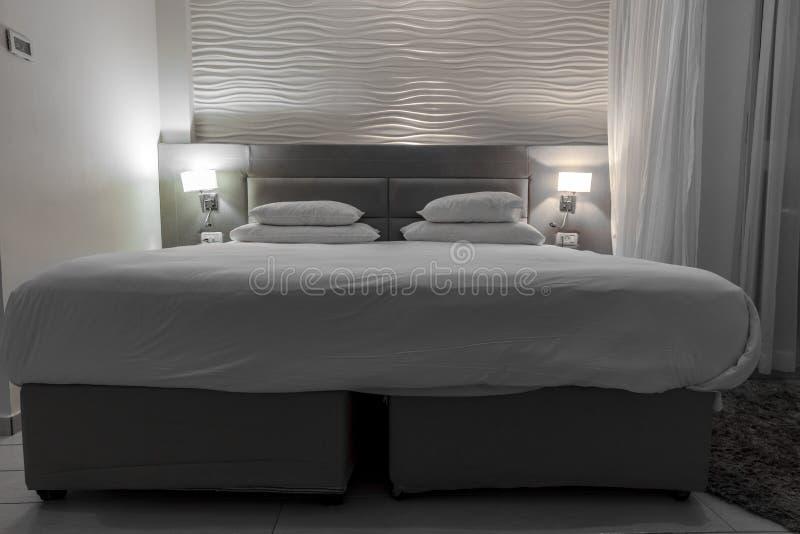 A cama de casal em uma sala de hotel com noite ilumina-se foto de stock