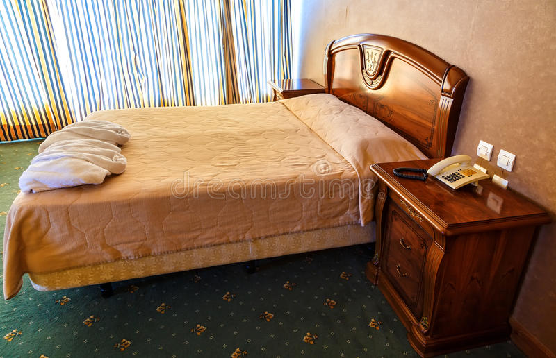 Cama de casal na sala de hotel com projeto do vintage foto de stock