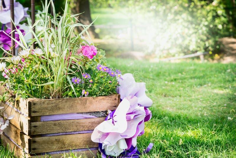 Cama de flor de madeira no parque com as flores coloridas da mola, fundo de um gramado e as árvores ensolarados imagens de stock royalty free