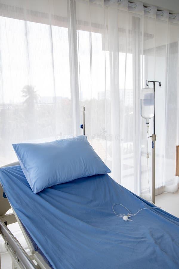 Cama de hospital con el soporte y el tubo del intravenoso foto de archivo