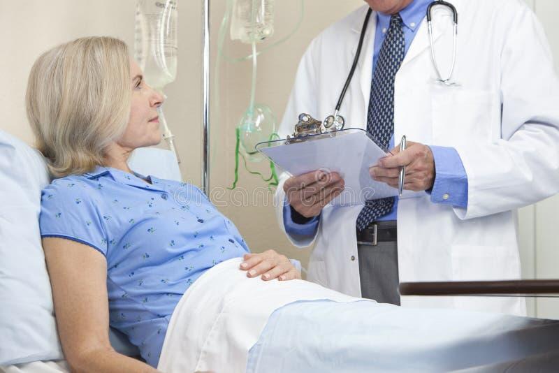 Cama de hospital paciente femenina mayor y doctor de sexo masculino fotos de archivo libres de regalías
