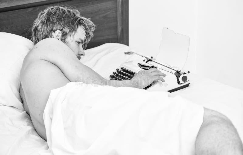 Cama de la endecha del escritor del hombre que trabaja en el nuevo libro El nuevo d?a trae ideas frescas El autor del escritor ut fotos de archivo