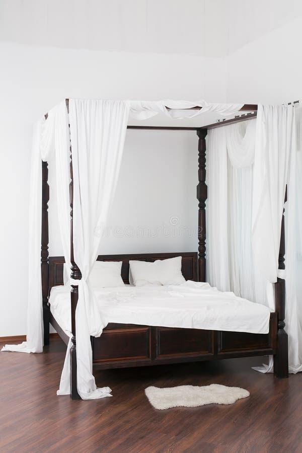 Cama de madeira do dossel e um couro cru branco no assoalho fotografia de stock