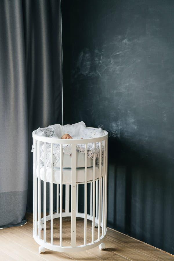 Cama de madera redonda para los bebés dentro del cuarto contra la perspectiva de una pared cretácea oscura Transforme moderno con imagen de archivo