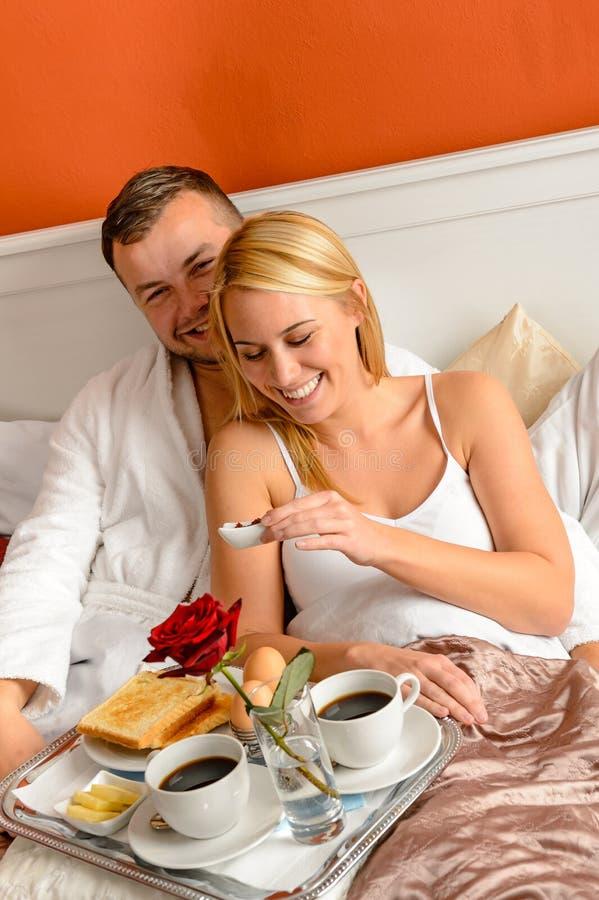 Cama de mentira de los amantes felices que come el desayuno romántico fotografía de archivo