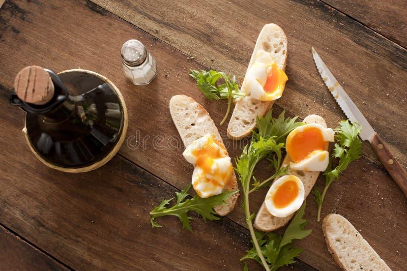 Cama de ovos cozidos duros e ervas na baguete foto de stock royalty free