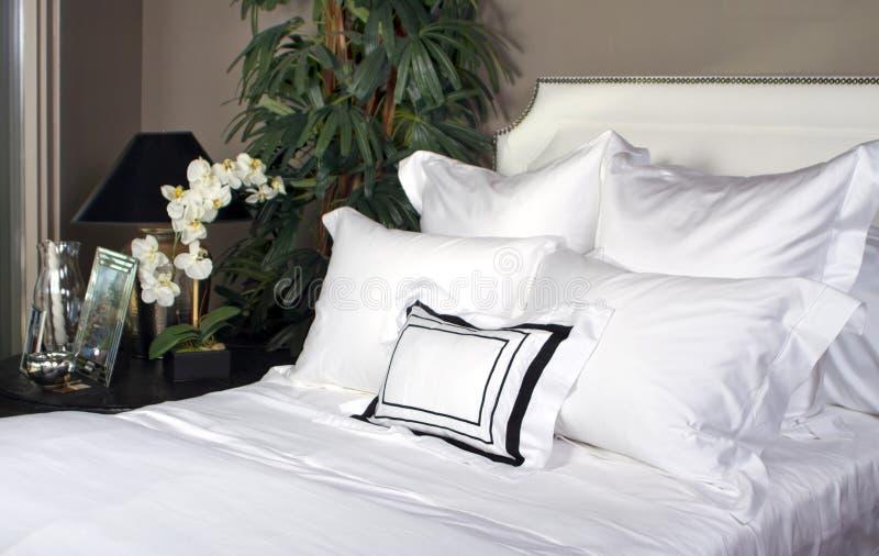 Cama del hotel y lino blanco imagenes de archivo