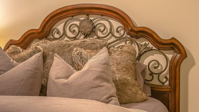 Cama del panorama con el cabecero de madera y del hierro labrado dentro del dormitorio de un hogar fotos de archivo