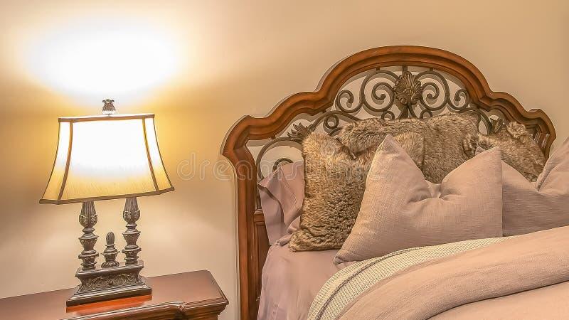 Cama del panorama con las almohadas mullidas contra el cabecero de madera y del hierro del worught fotografía de archivo libre de regalías