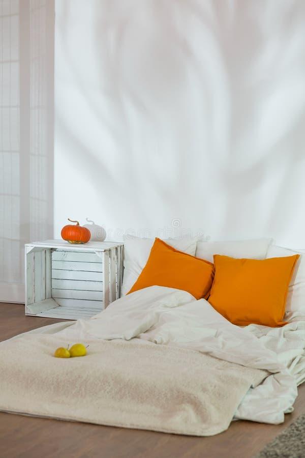 Cama desfeita no quarto simples do outono foto de stock