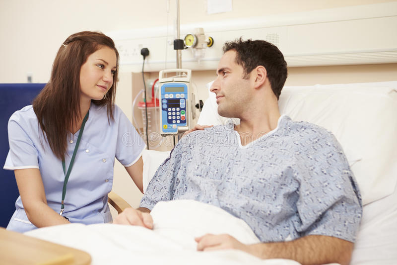 A cama do paciente de Sitting By Male da enfermeira no hospital foto de stock royalty free