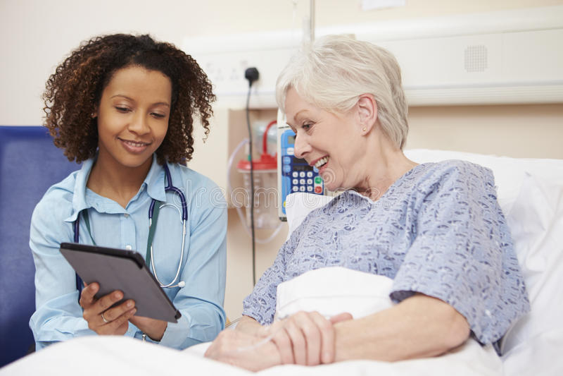 A cama do paciente do doutor Sitting By Female usando a tabuleta de Digitas foto de stock