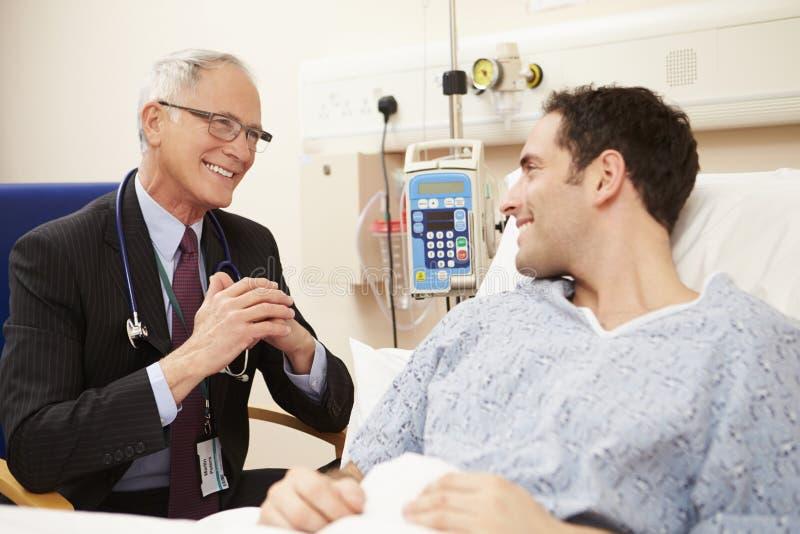 A cama do paciente do doutor Sitting By Male no hospital imagem de stock royalty free